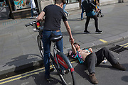 A handshake among youths as one young campaigner rests with his head on an Oxford Circus kerb on day 4 of protests by climate change environmental activists with pressure group Extinction Rebellion, on18th April 2019, in London, England.