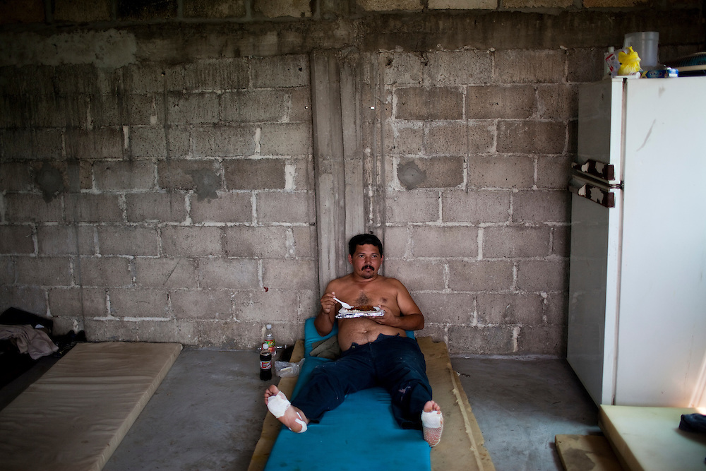 Jose Zunia eats in a migrant shelter in Tenosique, Tabasco.  He is from Honduras injured his feet walking 60 kilometers from the Mexican-Guatemalan border to this town, where he will ride on top of a freight train north to the border with the United States.  The trip for these migrants, mostly from Central America,  has become increasingly dangerous over the past several years as Mexico's drug war has raged and kidnappings and killings of migrants has increased.