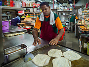 11 DECEMBER 2018 - SINGAPORE:  Making roti at a food shop in the Geylang neighborhood. The Geylang area of Singapore, between the Central Business District and Changi Airport, was originally coconut plantations and Malay villages. During Singapore's boom the coconut plantations and other farms were pushed out and now the area is a working class community of Malay, Indian and Chinese people. In the 2000s, developers started gentrifying Geylang and new housing estate developments were built.      PHOTO BY JACK KURTZ