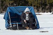 Middletown, New York - A man ice fishes at the Shawangunk Fish and Game Association pond during the association's annual contest on Feb. 8, 2014. ©Tom Bushey / The Image Works
