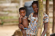 A teenage girl holds a younger girl in her arms in the village of Popoko, Bas-Sassandra region, Cote d'Ivoire, on Sunday March 4, 2012.
