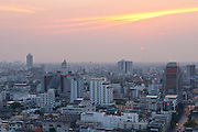 Sunset over downtown Bangkok with haze for agricultural burning; from rooftop restaurant of the Siam@Siam Hotel, Thailand.