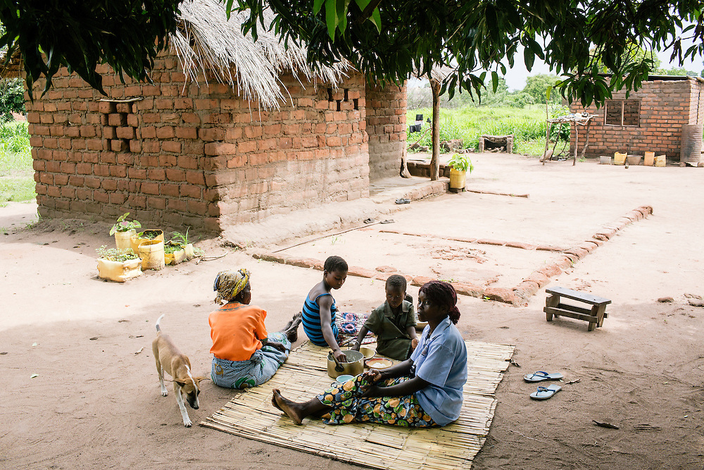Enny Mungawo and her family, including her mother Selia Zulu, and two of her four children, Ruth, 13, and David, 6, sit down for lunch at their homes rural Zambia. Mungawo was able to build a second place for her and her children after earning more money by farming organically, part of a partnership with COMACO, a organic agriculture business with facilities in Chipata, Zambia. Mungawo, a lead farmer with COMACO, is a single mom, but with the money she makes from selling her crops and teaching others how to farm better organically, she is able to support her four children and mother as well as send her children to school. As part of her partnership with COMACO, she also received a small stove which can cook just as well as the traditional Zambian fire pit, but uses substantially less wood, keeping more trees from being chopped down.