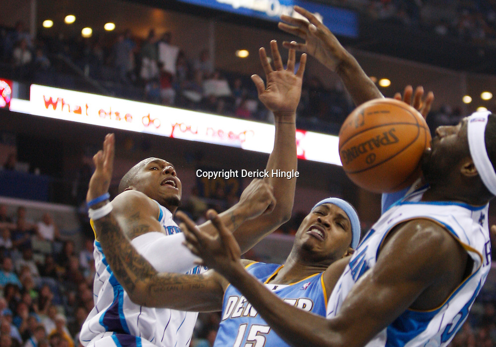 Mar 12, 2010; New Orleans, LA, USA; New Orleans Hornets forward David West (left) knocks the ball away from Denver Nuggets forward Carmelo Anthony (15) as forward Julian Wright (32) defends during the first half at the New Orleans Arena. Mandatory Credit: Derick E. Hingle-US PRESSWIRE