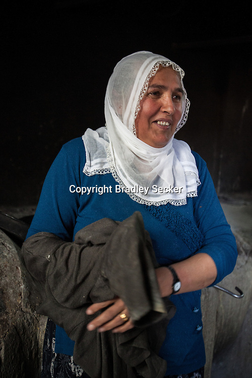 Ayten, 50, from Diyarbakir, bakes bread at a centre for women, nicknamed the 'laundry house'. Ayten was married at around 15 years old, and has 10 children. Women can wash clothes, bake bread, and receive education and advice from doctors and social workers free of charge. Diyarbakir, Turkey