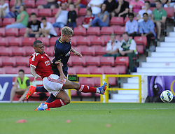 Swindon Town's  Nathan Byrne tackles Southampton's Lloyd Isgrove - Photo mandatory by-line: Joe Meredith/JMP - Mobile: 07966 386802 21/07/2014 - SPORT - FOOTBALL - Swindon - County Ground - Swindon Town v Southampton