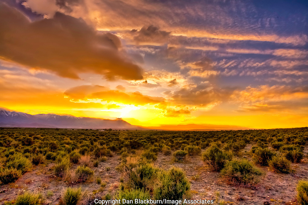 Setting Sun over the Sierra Illuminates land and sky and clouds in the Owens Valley of California