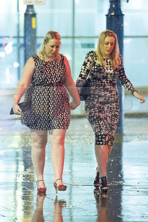 © Licensed to London News Pictures . 17/03/2013 . Manchester , UK . Two women walk hand in hand carefully on the slippery pavement . Evening revellers out in the rain and snow in to the early hours , in Manchester this St Patrick's Day morning (17th March) . Photo credit : Joel Goodman/LNP
