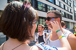 London, July 8th 2017. Thousands of LGBT+ revellers take part in the annual Pride in London parade under the banner #LoveHappensHere. PICTURED: A woman applies glitter to a man's face.