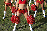 Cheerleaders with pom poms on field low section