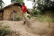 Patience Nsona sweeps dirt into a hole outside her home in the village of Kinsiesi, Bas-Congo province, Democratic Republic of Congo on Saturday June 18, 2011.