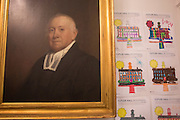 A portrait of Manasseh Cutler, one of Ohio University's founding fathers, hangs on a wall in Cutler Hall along with pictures of Cutler Hall colored by elementary school students in Cutler Hall during the Cutler Hall Bicentennial celebration on October 21, 2016.