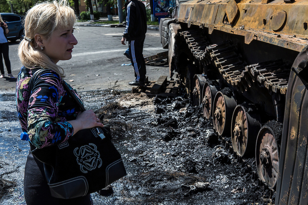 MARIUPOL, UKRAINE - MAY 10: A woman looks at a burned tank a day after deadly clashes on May 10, 2014 in Mariupol, Ukraine. A referendum on greater autonomy is planned for the region tomorrow. (Photo by Brendan Hoffman/Getty Images) *** Local Caption ***