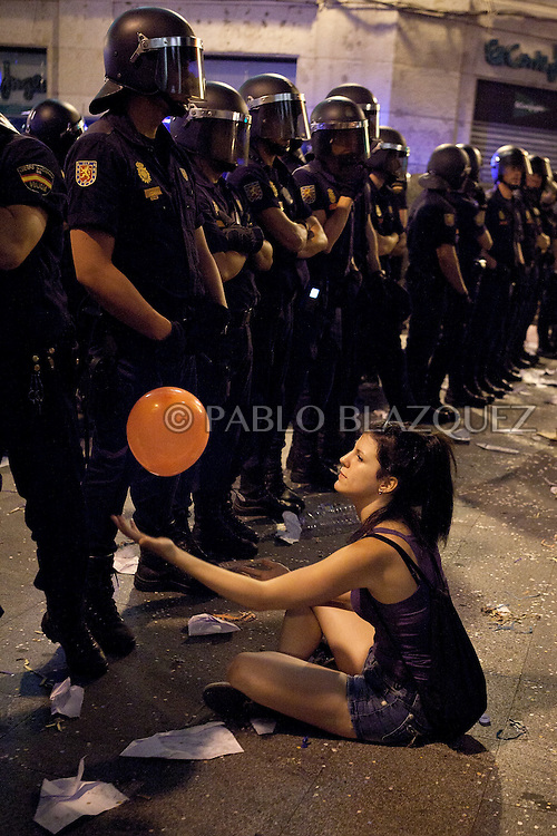 A girl plays with a balloon in front of Spanish riot police who prevents 'indignant' protesters from gaining access to Puerta del Sol Square in Madrid on August 3, 2011, after being evicted in a dawn raid. Hundreds of protesters crammed into each of the sidestreets leading to the central square of Puerta del Sol, birthplace of a nationwide protest against the suffering caused by Spain's economic blight. Lines of riot police crossed their arms and stood in front of the demonstrators, who gathered in swelling numbers in response to Facebook and Twitter pleas for a mass response to their eviction.