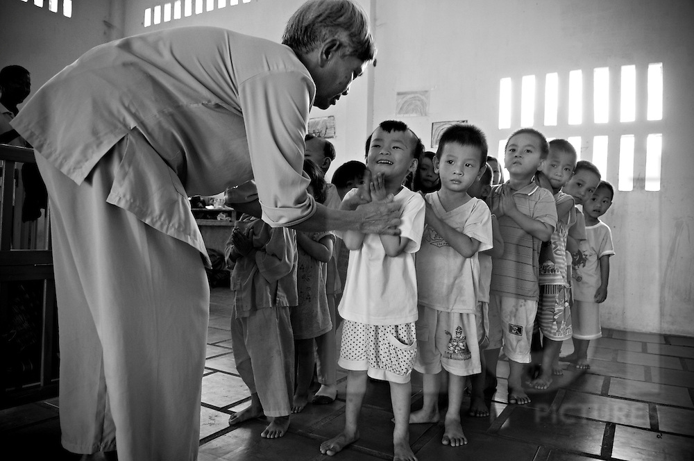 A group of young vietnamese orphans line up and fold their hand to tell a prayer. Khanh Hoa province, Vietnam, Asia