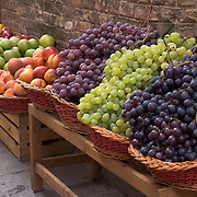 Fresh grapes in wicker baskets outside shop in Siena, Italy<br />