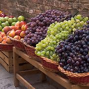 Fresh grapes in wicker baskets outside shop in Siena, Italy<br />