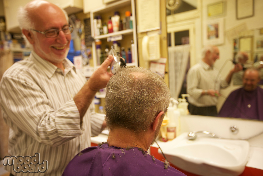 Happy man cutting senior customer's hair with razor