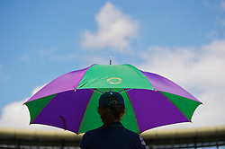 LONDON, ENGLAND - Tuesday, June 29, 2010: A bill girl holds a Wimbledon umbrella to sheild a player from the heat of the sun on day eight of the Wimbledon Lawn Tennis Championships at the All England Lawn Tennis and Croquet Club. (Pic by David Rawcliffe/Propaganda)