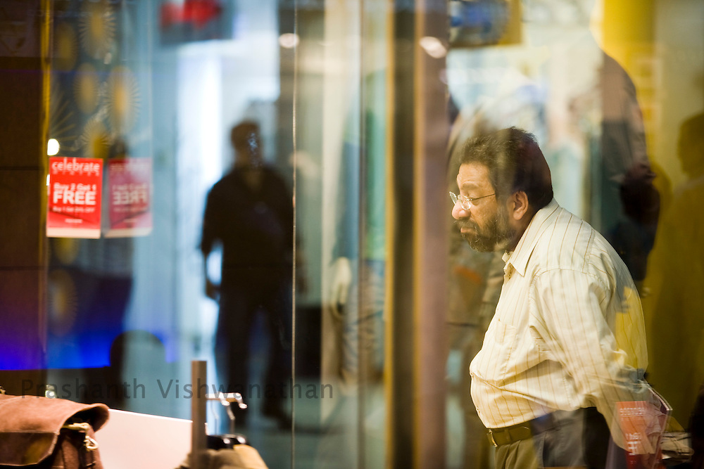 A man looks at a freebie offer at an outlet inside the Inorbit Mall Malad, in Mumbai, on Sunday Dec. 28, 2008.  Photographer:Prashanth Vishwanathan