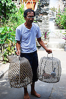 Mr Sarga carrying his pigeons in 2 cages.