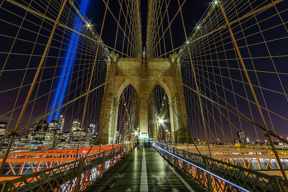 September 11th on the Brooklyn Bridge in New York City as the city lights and the 911 Memorial shines brightly in the night sky.