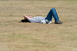 ©Licensed to London News Pictures 12/08/2020             Greenwich, UK. A man sunbathing in jeans and a t-shirt. The hot heatwave weather continues in London and the South East today with people out and about in Greenwich park, Greenwich, London. Photo credit: Grant Falvey/LNP
