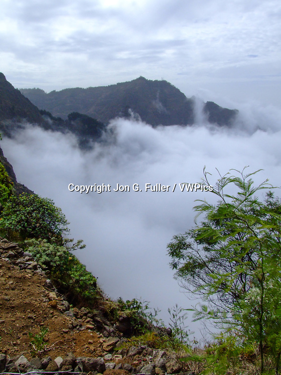 Low clouds obscure the view of the valleys and canyons below the ridge tops in the mountains of Santo Antao, Republic of Cabo Verde on the Rua de Corda from Porto Novo to Ribeira Grande.