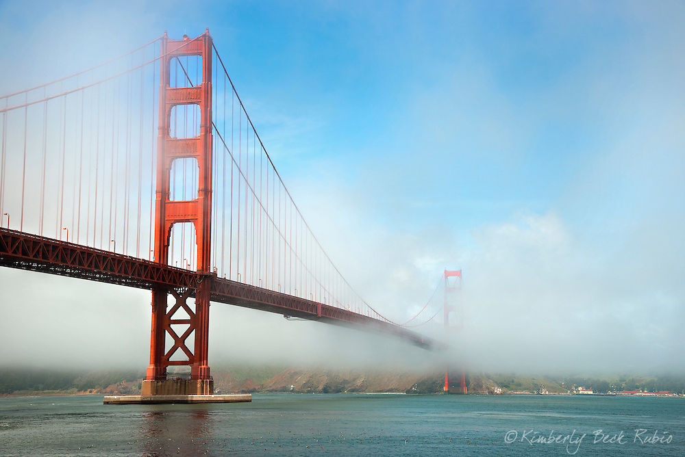 San Francisco's Golden Gate Bridge emerging from the fog on a spring day. Taken from Fort Point, San Francisco, looking toward Cavallo Point and Marin Headlands in Marin, California.