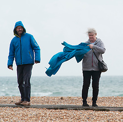 © Licensed to London News Pictures. 08/03/2019. Folkestone, A lady having some trouble getting her coat on in the seafront wind. A cloudy and windy afternoon at Folkestone sea front today with the weekend weather forecasters predicting 70mph winds with heavy rain.Photo credit: Grant Falvey/LNP