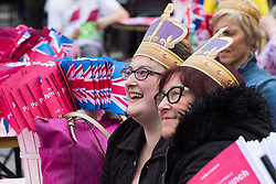 Trafalgar Square, London, June 12th 2016. Rain greets Londoners and visitors to the capital's Trafalgar Square as the Mayor hosts a Patron's Lunch in celebration of The Queen's 90th birthday. PICTURED: Two women enjoy the entertainment on stage.
