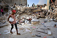 Woman passing by dead bodies  in downtown Port-au-Prince after the earthquake in Haiti on January 18, 2010.