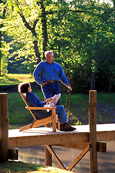 Stock photo of  an older man and woman sitting on a dock enjoying the outdoors