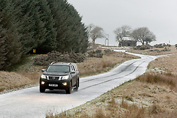 © Licensed to London News Pictures. 09/11/2019. Builth Wells, Powys, Wales, UK. A motorist drives through a wintry landscape. Temperatures plunge to below zero during the night and snow falls this morning on the high land of the Mynydd Epynt range near Builth Wells in Powys, Wales, UK.Photo credit: Graham M. Lawrence/LNP
