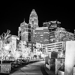 Black and white photo of the Charlotte skyline at night with Romare Bearden Park. Charlotte, North Carolina is a major city in the Eastern United States of America. Includes Bank of America Corporate Center, Bank of America Plaza, and 121 West Trade buildings.