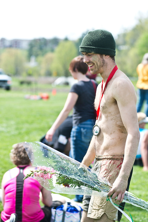Steven Malueg, a sophomore at Ohio University studying marine biology, walks back towards the crowd after accepting the award for the best male overall completion time during the Race for a Reason Mud Run, Saturday, April 27, 2013. The course included a four-mile run up to the old Army ROTC Course at the Ridges, through the Radar Hill Trail and back to Tail Great Park across from Peden Stadium. Race for a Reason, Race 4 A Reason, Annual Events, Events, Students, Faculty & Staff