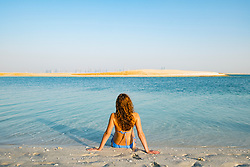 Woman on beach at The Island Lebanon beach resort on a man made island, part of The World off Dubai coast in  United Arab Emirates