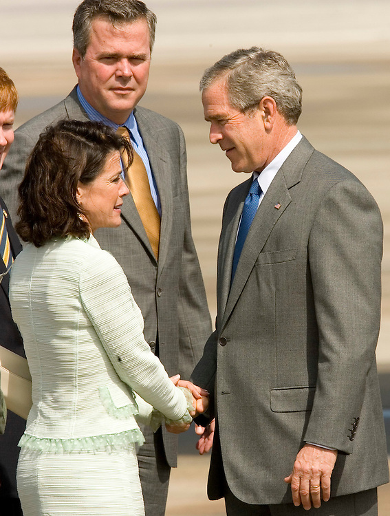 Congresswoman Katherine Harris, left, speaks with President George W. Bush, right, as Florida Gov. Jeb Bush watches on after the president's arrival at MacDill Air Force Base in Tampa, Fla. on Tuesday, May 9, 2006.(AP Photo/Scott Audette)