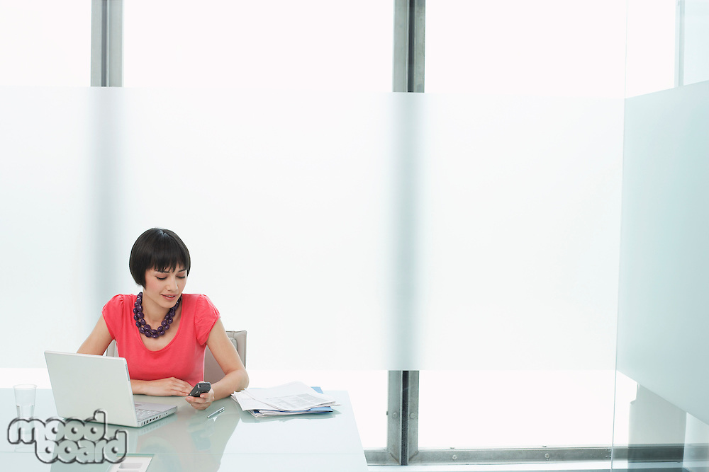 Woman using mobile phone and laptop in modern cubicle