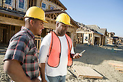 Two construction workers using mobile phone on construction site