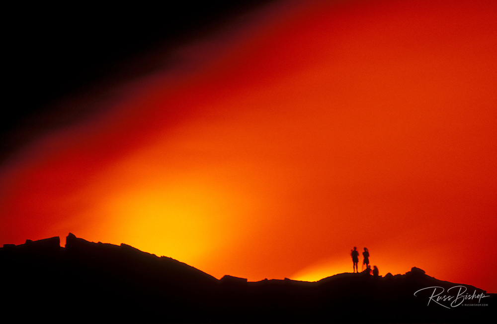 Hikers watching lava flow enter the Pacific Ocean at night, Hawaii Volcanoes National Park, Hawaii USA
