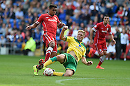 Tom Adeyemi of Cardiff city (l)  is fouled by Michael Turner of Norwich city for which he is booked. Skybet football league championship match, Cardiff city v Norwich city at the Cardiff city Stadium in Cardiff, South Wales on Saturday 13th Sept 2014<br /> pic by Andrew Orchard, Andrew Orchard sports photography.
