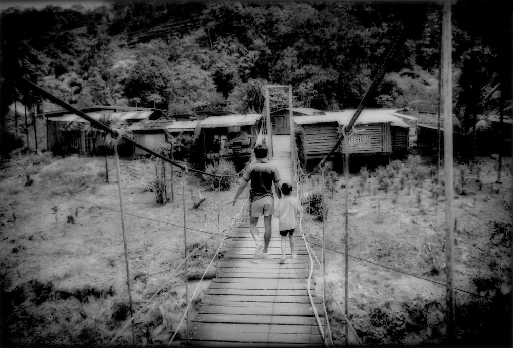 Iban father returns to Rumah Enggin Longhouse with his son across a suspension bridge, near Kapit, Sarawak, Malaysian Borneo.
