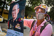 18 FEBRUARY 2014 - BANGKOK, THAILAND: A Thai anti-government protestor holds up a portrait of Bhumibol Adulyadej, the King of Thailand, during a protest in Bangkok. Many of the anti-government protestors are monarchists who allege the elected government does not adequately support the monarchy. Anti-government protestors aligned with Suthep Thaugsuban and the People's Democratic Reform Committee (PDRC) clashed with police Tuesday. Protestors opened fire on police with at rifles and handguns. Police returned fire with live ammunition and rubber bullets. The Bangkok Metropolitan Administration's Erawan Emergency Medical Centre reported that three civilians and a policeman were killed and 64 others were injured in the clashes between police and protesters.    PHOTO BY JACK KURTZ
