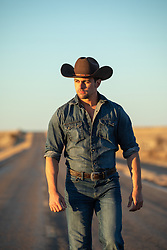 cowboy at sunset walking on a road