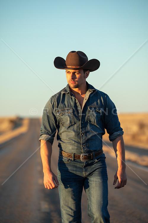 cowboy at sunset walking on a road