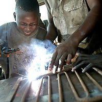 Benin, Cotonou September 2003 - Children learning how to weld.   Some types of work make useful, positive contributions to a child's development. Work can help children learn about responsibility and develop particular skills that will benefit them and the rest of society. Often, work is a vital source of income that helps to sustain children and their families. However, across the world, millions of children do extremely hazardous work in harmful conditions, putting their health, education, personal and social development, and even their lives at risk