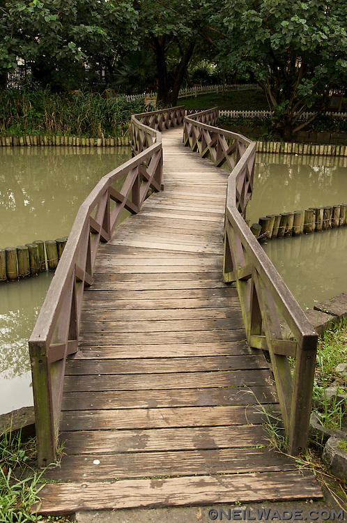 A crooked, Chinese style wooden foot bridge at the Taipei Botanical Gardens in Taipei, Taiwan.
