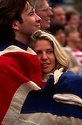 While crowds wave Union Jack flags, a young couple too young to remember a world war comfort themselves wrapped in a large union jack flag, to remember the 50th anniversary of VE (Victory in Europe) Day on 6th May 1995. In the week near the anniversary date of May 8, 1945, when the World War II Allies formally accepted the unconditional surrender of the armed forces of Germany and peace was announced to tumultuous crowds across European cities, the British still go out of their way to honour those sacrificed and the realisation that peace was once again achieved. Street parties now - as they did in 1945 - played a large part in the country's patriotic well-being...