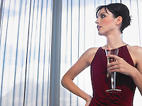 Woman wearing elegant dress with champagne in front of window